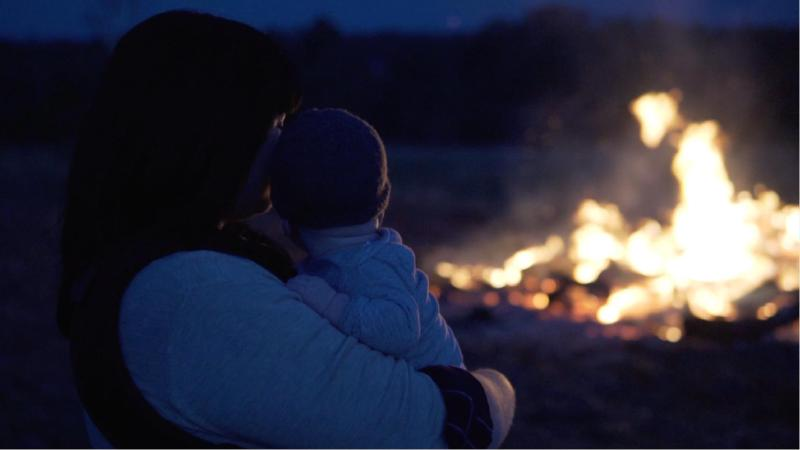 Mother and baby watching a bonfire at night