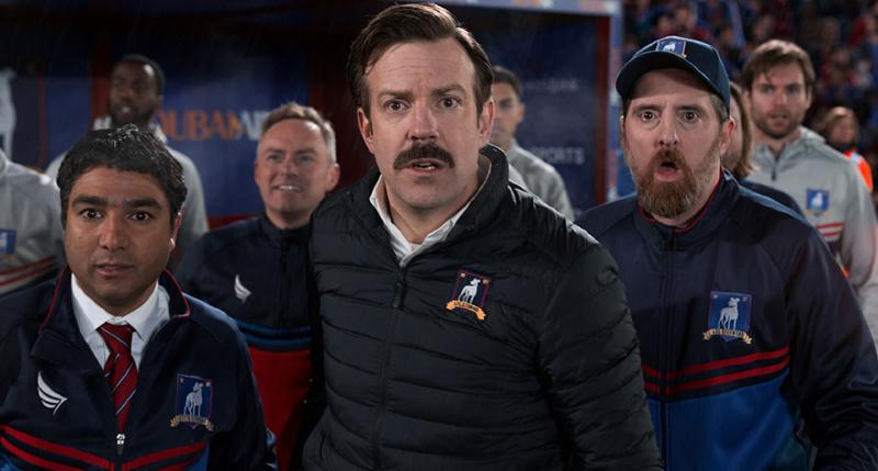 Ted Lasso and his teammates watching a football game